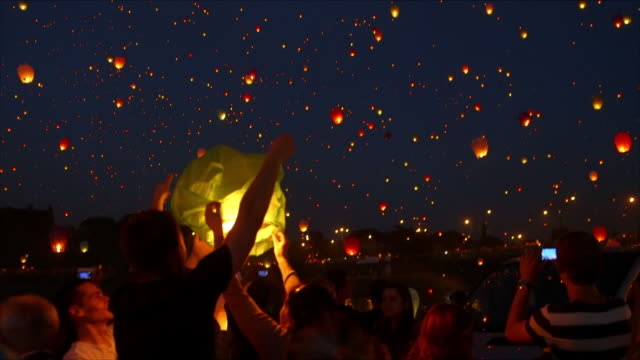 people watch as lanterns are released, poland - in der luft schwebend stock-videos und b-roll-filmmaterial