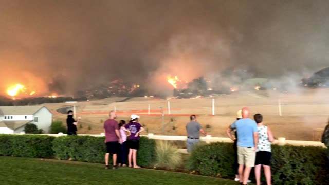 People watch as the Holy Fire burns in Cleveland National Forest near homes on August 9 2018 in Corona California
