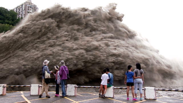 people watch flood waters burst from shimen dam in taiwan after typhoon dujuan made landfall - energia idroelettrica video stock e b–roll