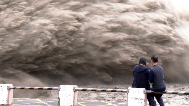 People watch flood waters burst from Shimen dam in Taiwan after typhoon Dujuan made landfall