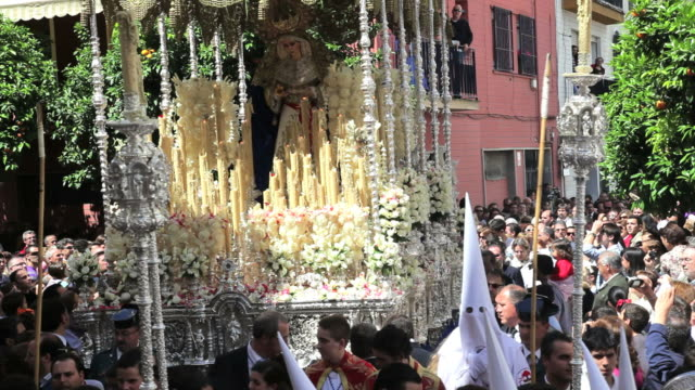 people watch the costaleros bearing a large trono in a procession with the hooded nazarenos through the streets of malaga, andalucia, spain, europe - holy week stock videos & royalty-free footage