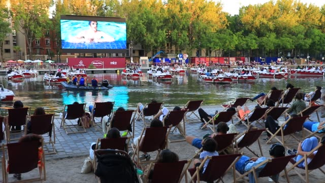 "people watch the film from boats and desk chairs during paris plages launch of ""le cinema sur l'eau"" with the screening of ""le grand bain"" at bassin... - film industry stock videos & royalty-free footage"