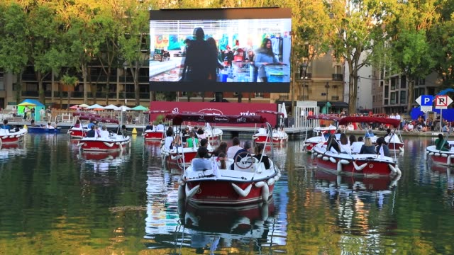 "people watch the film from boats during paris plages launch of ""le cinema sur l'eau"" with the screening of ""le grand bain"" at bassin de la villette... - 怠惰点の映像素材/bロール"