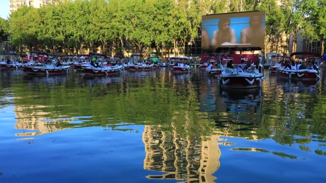 """people watch the film from boats during paris plages launch of """"le cinema sur l'eau"""" with the screening of """"le grand bain"""" at bassin de la villette... - laziness stock videos & royalty-free footage"""