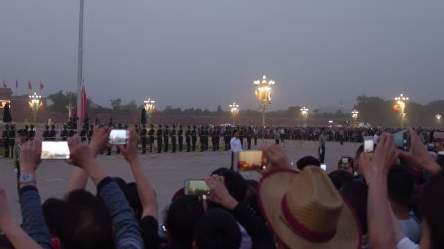 vidéos et rushes de people watch the flaglowering ceremony at tiananmen square in a sandstorm on may 4 2017 in beijing china - porte de la paix céleste