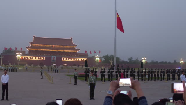 vídeos y material grabado en eventos de stock de people watch the flaglowering ceremony at tiananmen square in a sandstorm on may 4 2017 in beijing china - puerta de la paz celestial de tiananmen