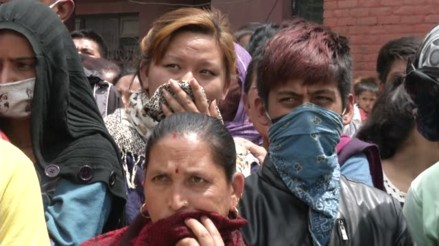 People watch while Nepali Army search for bodies and possessions after buildings collapsed / A major 7 9 earthquake hit Kathmandu midday on Saturday...