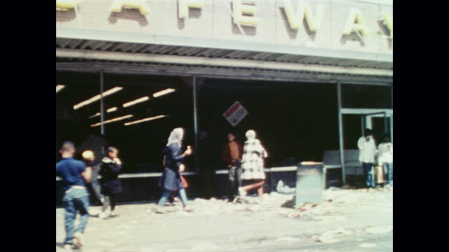 vídeos y material grabado en eventos de stock de people watching a fire burn from the top story of a building across the street, as pedestrians and looters walk along. kids play in the streets as... - 1968