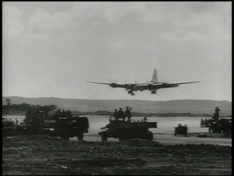 People watching as B29 Superfortress bomber aircraft approaching runway for landing landing male on tower waving another B29 attempting to land on...