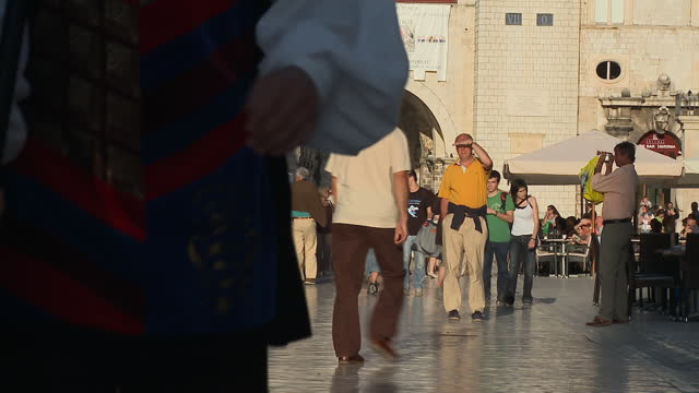 WS People watching as three men in period costume, one of them playing a snare drum, walk through The Stradun/ Dubrovnik, Dalmatia