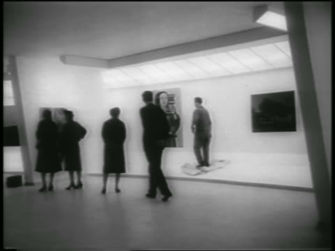 b/w 1959 people watching as workman adjusts artwork in guggenheim museum / nyc - 美術館点の映像素材/bロール