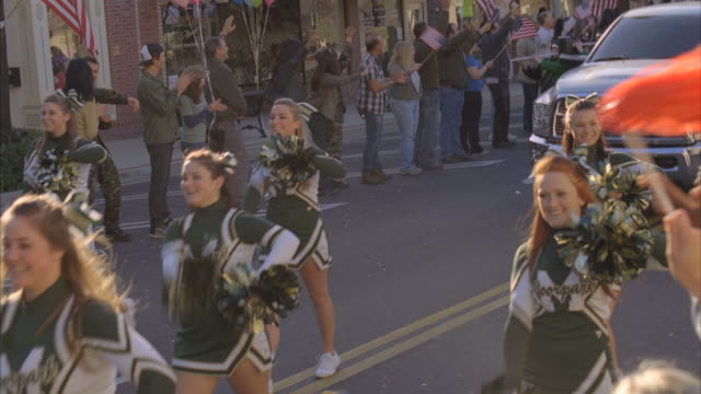 ws people watching parade of cheerleaders with truck pulling float during parade / fillmore, california, usa - cheerleader stock videos and b-roll footage