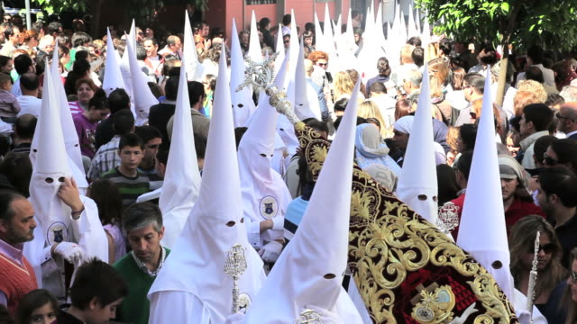 people watching the white hooded nazarenos parade during the celebration of semana santa a holy week in malaga spain, europe - festwagen stock-videos und b-roll-filmmaterial