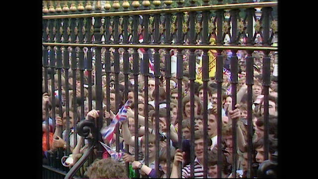 people wave flags and sing while they wait at the railings of buckingham palace on the day of the wedding of prince charles and lady diana spencer;... - boundary stock videos & royalty-free footage
