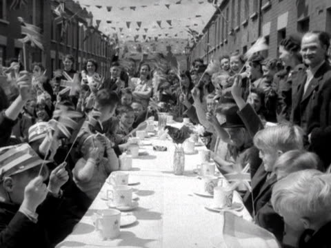 people wave flags during a street party for the coronation of elizabeth the second 1953 - street party stock videos and b-roll footage