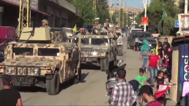 people wave hezbollah flags as a convoy carrying the bodies of fighters killed in clashes along the lebanesesyrian border drives past on july 30 2017... - hezbollah stock videos & royalty-free footage