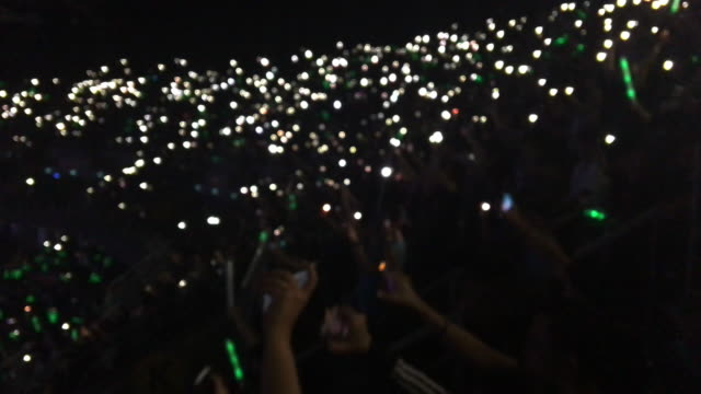 vídeos de stock e filmes b-roll de people wave light from smart phone up at the concert - evento de entretenimento