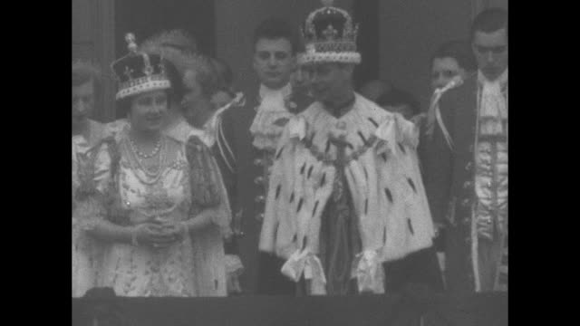 people waving at center gate of buckingham palace with royals on balcony beyond / george vi and queen elizabeth repeatedly bowing to crowd after... - crown headwear stock videos and b-roll footage