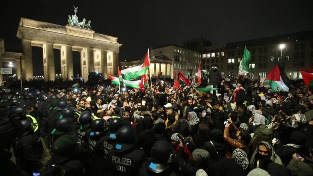 People waving Palestinian and Turkish flags gather in front of the Brandenburg Gate to protest against US President Donald Trump's announcement to...