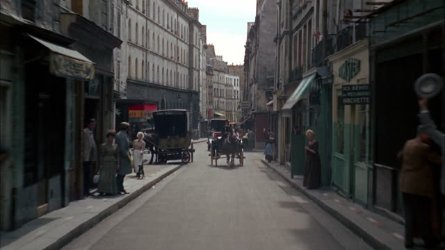 ws pov people waving to camera moving through city streets / paris, france - rievocazione video stock e b–roll