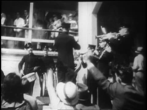b/w 1928 people waving to people on deck of ocean liner as band plays in foreground / newsreel - 1928 stock-videos und b-roll-filmmaterial