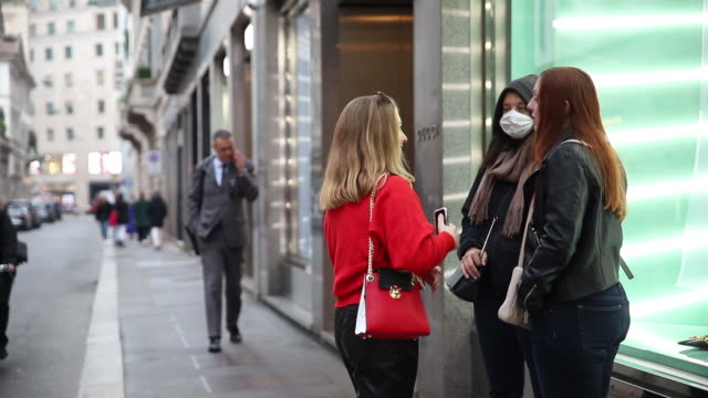 vídeos de stock e filmes b-roll de people wear face masks during the shutdown from the coronavirus in milan italy on tuesday february 25 2020 italy never appears far from a recession... - vírus da gripe