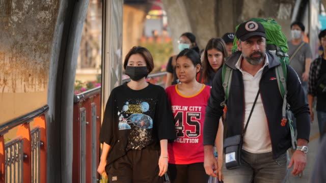 vidéos et rushes de people wear masks in the victory monument area after the first coronavirus patient died in thailand. - épidémie