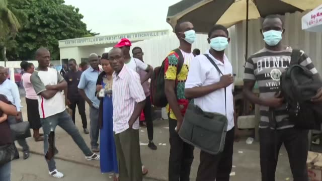 people wear masks outside the hospital where ivory coast's first confirmed case of new coronavirus is reportedly being treated - africa stock videos & royalty-free footage