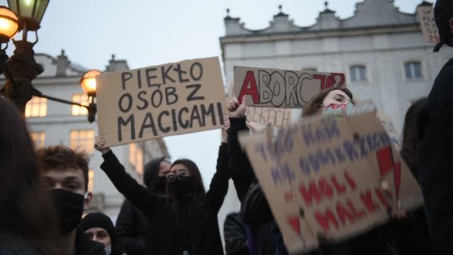 people wear protective face masks shaking signs and chanting as they protest for the fourth day against the constitutional court ruling on tightening... - polonia video stock e b–roll