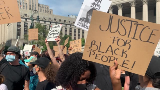 people wear protective masks and coverings as a woman holds a sign with justice for black people written and as people chant i can't breathe as... - george floyd stock videos & royalty-free footage