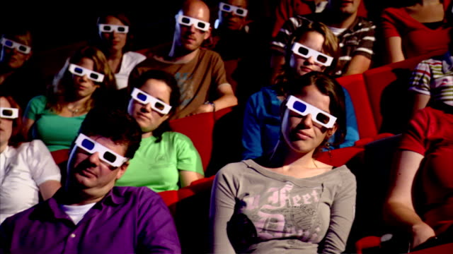 vídeos de stock, filmes e b-roll de ms pan people wearing 3d glasses in theatre  - óculos de terceira dimensão