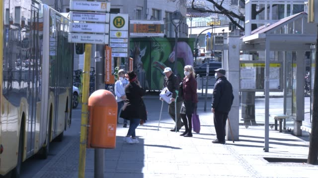 people wearing a protective face mask wait for the public bus at bahnhof zoo district during the coronavirus crisis on april 9, 2020 in berlin,... - bus billboard stock videos & royalty-free footage