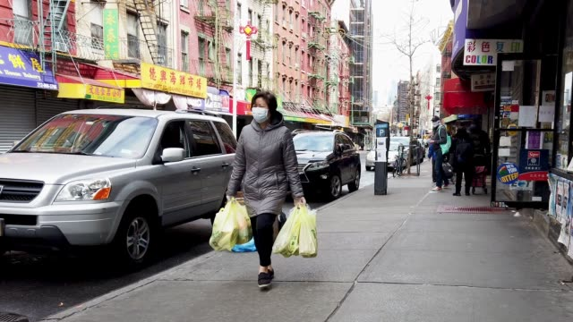 people wearing a protective masks are seen walking in chinatown, new york city on april 04, 2020. - chinatown stock videos & royalty-free footage
