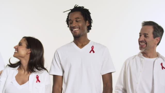 people wearing aids awareness ribbons - aids awareness ribbon stock videos & royalty-free footage