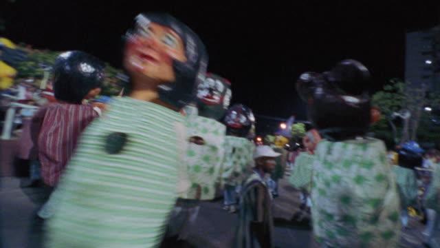 T/L, DS, People wearing big head carnival costumes on street parade at night, Santiago de Cuba, Cuba