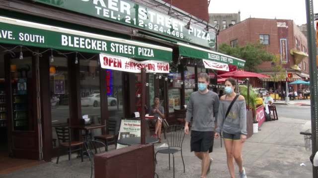 people wearing face coverings are out and about on 7th avenue south while others dine outdoors at bleecker street pizza on september 26 2020 in the... - scott mcpartland stock videos & royalty-free footage