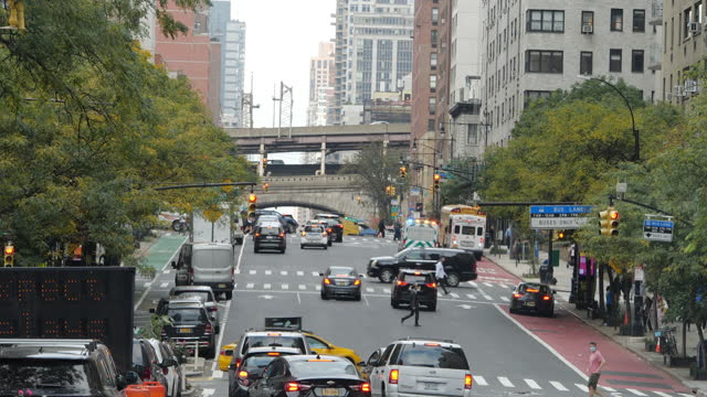 people wearing face mask crossing street and ambulance with siren blaring running in the background in new york city in the autumn amid the 2020... - noise stock videos & royalty-free footage