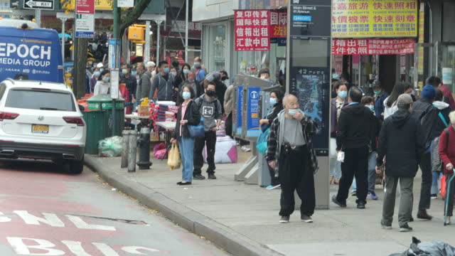 vídeos de stock e filmes b-roll de people wearing face mask shopping in flushing chinatown, queens, new york amid the 2020 global coronavirus pandemic. - cultura chinesa