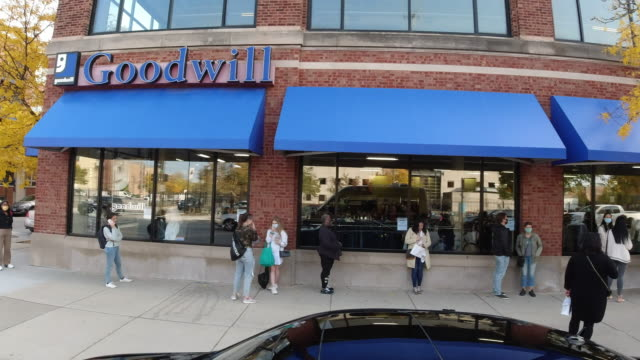 people wearing face mask waiting outside the goodwill store in chicago. - fare la fila video stock e b–roll