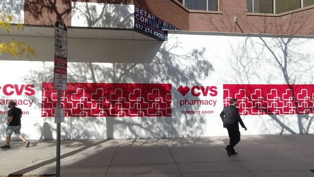 people wearing face mask walking past a wall painted with the logo of the chain pharmacy store, cvs, amidst the 2020 global coronavirus pandemic. - cvsケアマーク点の映像素材/bロール