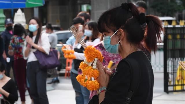 people wearing face masks at the erawan shrine on august 6, 2020 in bangkok, thailand. - エラワン聖堂点の映像素材/bロール