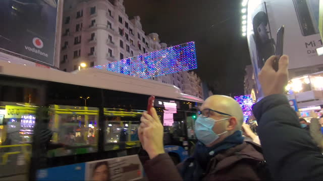people wearing face masks gather at the iconic callao square with their mobile phones to watch and record the switching-on of the street christmas... - マドリード グランヴィア通り点の映像素材/bロール