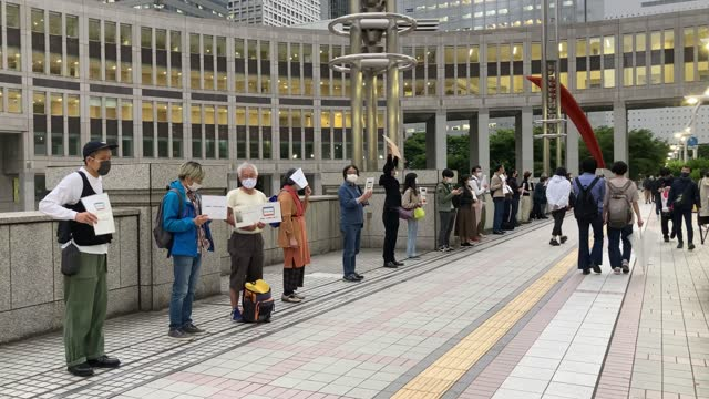 people wearing face masks hold placards as they demonstrate against tokyo's coronavirus restrictions outside of the metropolitan government building... - cinematography stock videos & royalty-free footage