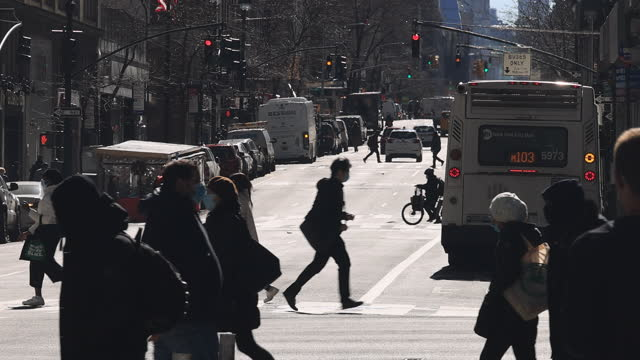 people wearing facemask cross lexington avenue amidst pandemic of covid-19. - road marking stock videos & royalty-free footage
