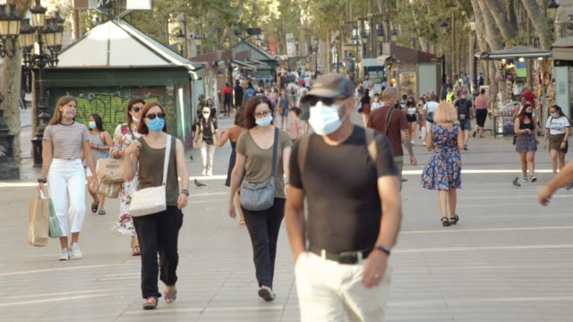 people wearing masks at barcelona ramblas iconic street. coronavirus crisis during summer 2020 - spain stock videos & royalty-free footage