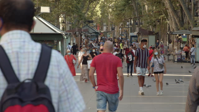 people wearing masks at barcelona street during covid-19. ramblas iconic street at summer 2020 - spanien stock-videos und b-roll-filmmaterial