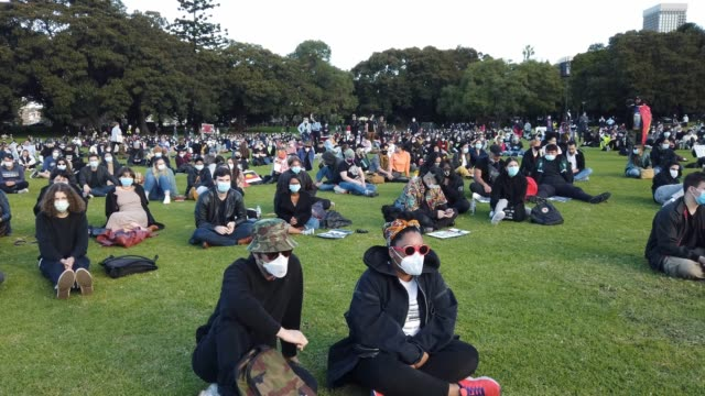 people wearing masks sitting on the grass listen to a speaker as activists gather in the domain to rally against aboriginal and torres strait... - social gathering stock videos & royalty-free footage