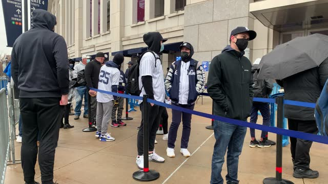 people wearing masks wait to enter yankee stadium in the bronx for the opening day of the major league baseball season on april 01, 2021 in new york... - 1日目点の映像素材/bロール