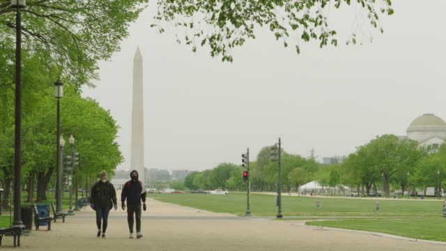 people wearing masks walk on the mall with washington monument in the background - washington dc stock videos & royalty-free footage