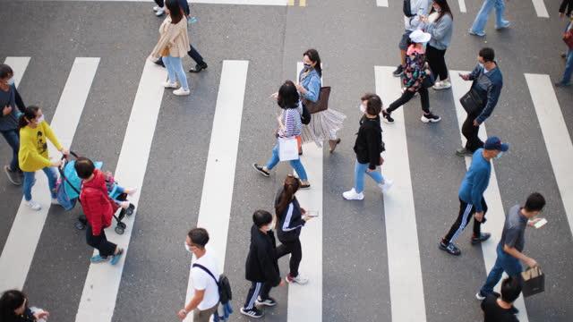 people wearing masks walking on zebra crossing - taiwan stock videos & royalty-free footage